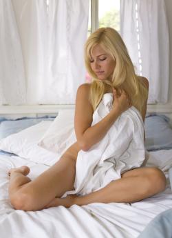 Schne nackte Frau auf dem Bett liegend Stockfoto