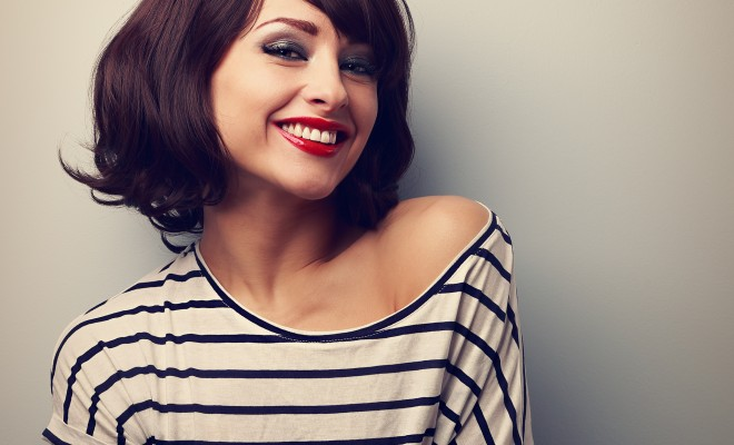 Happy laughing young woman with short hair in fashion blouse