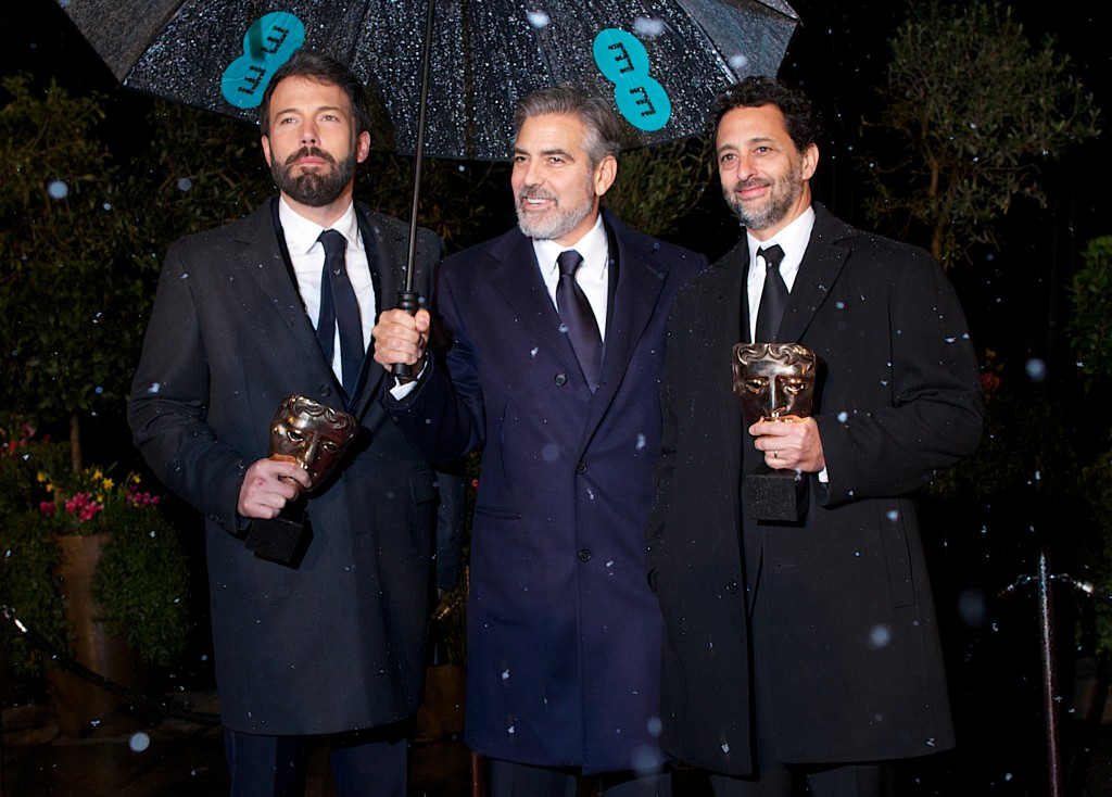 (L-R) US actor and directors Ben Affleck and George Clooney and US actor Grant Heslov hold their awards as they pose arriving for the BAFTA British Academy Film Awards after party in London on February 10, 2013. AFP PHOTO / ANDREW COWIE        (Photo credit should read ANDREW COWIE/AFP/Getty Images)