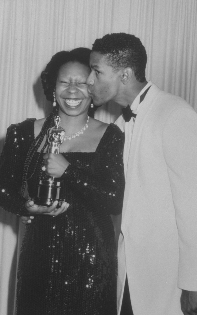 Actress Whoopi Goldberg holding her Oscar for Best Supporting Actress & being smooched by actor Denzel Washington at Academy Awards ceremony.  (Photo by Kevin Winter/DMI/The LIFE Picture Collection/Getty Images)