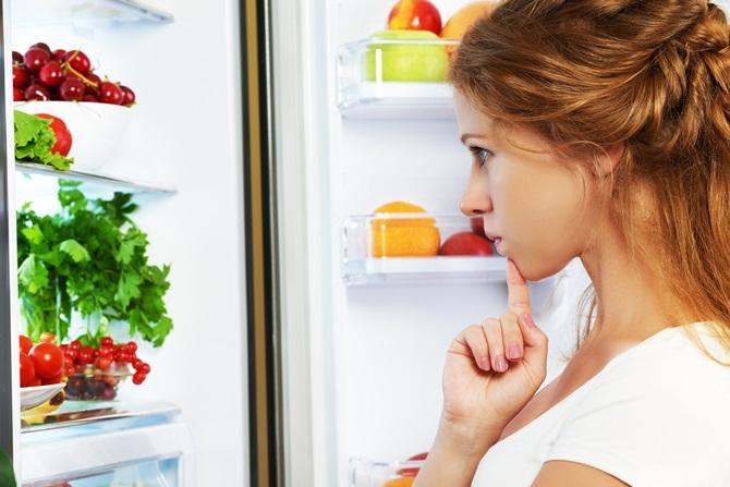 femeie se uita in frigider