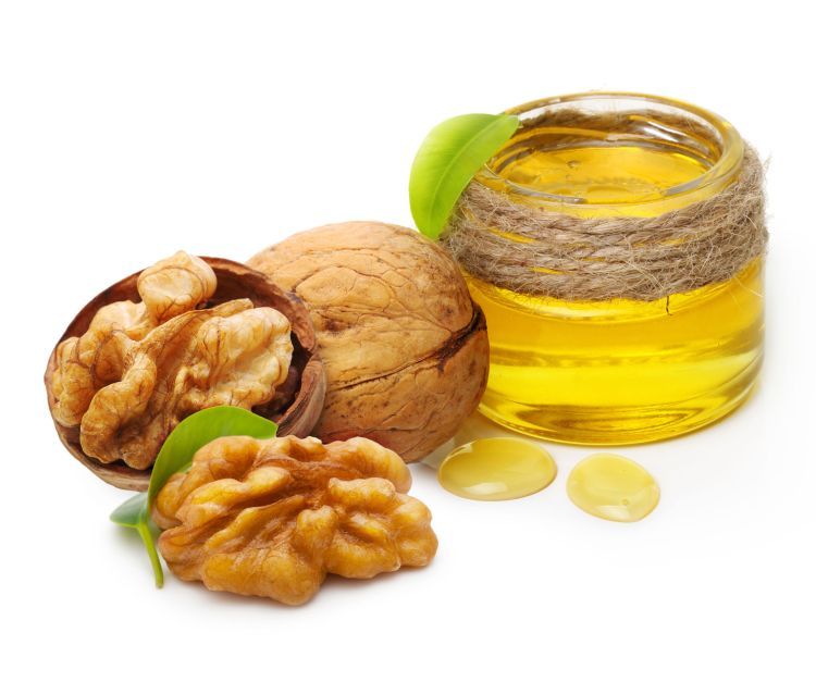 61262742 – walnut oil and nuts with leaf isolated on white background