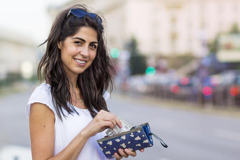 femeie pe strada cu portofel