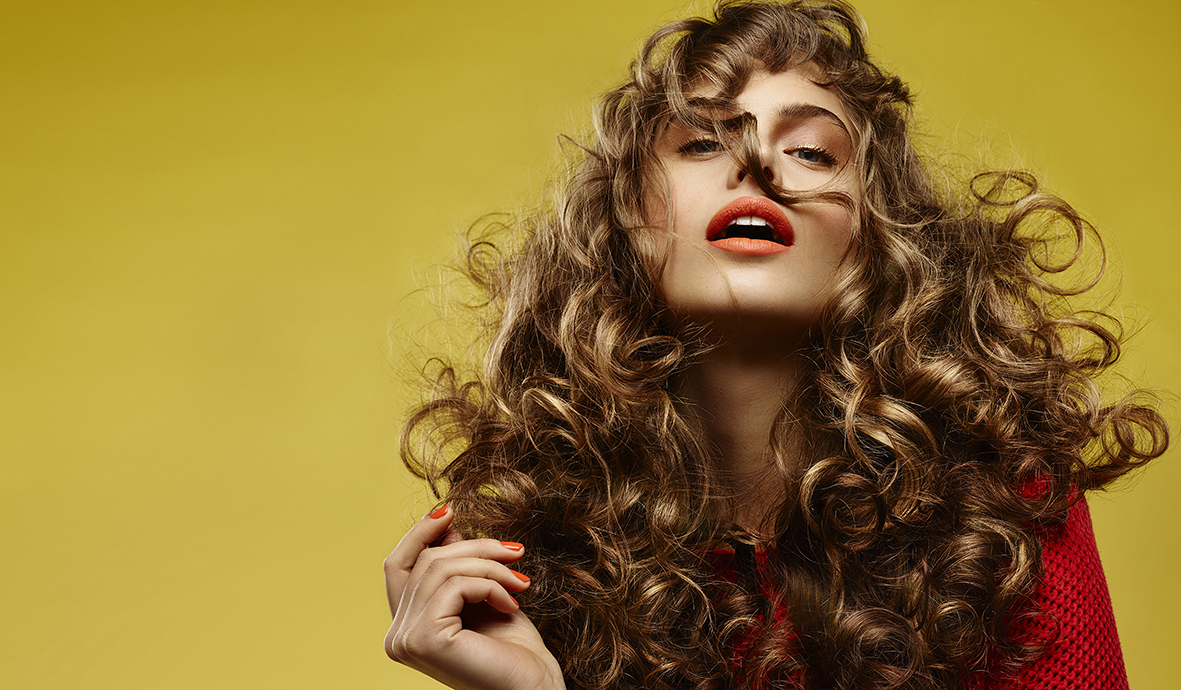 Girl with long wavy, full curly  brown hair, wearing a red top, orange lipstick