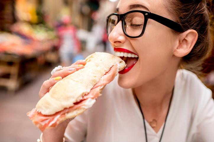 femeie mananca sendvis